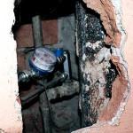 Rodzina Rychterowiczów pokazuje dziurę w ścianie, po tym jak założono im wodomierz.