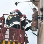 Słupeccy strażacy demontują figurę Św. Wawrzyńca ze ściany redakcji Gazety Słupeckiej.